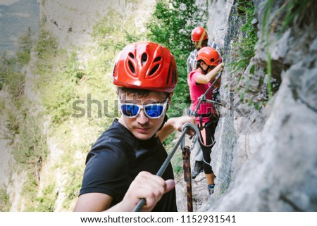 Friends who are climbing along a via ferrata #1152931541