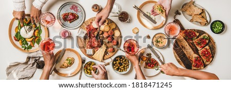 Friends wine and snacks party. Flay-lay of peoples hands with rose wine and food over table with cheese, fruit, smoked meat, tomato brushettas, buratta salad, top view. Wine tasting, gathering concept