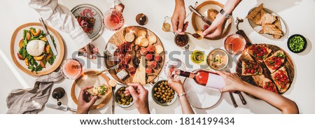 Friends wine and snacks party. Flay-lay of rose wine in glasses, cheese, fruit, meat, tomato brushettas, buratta salad and peoples hands over white table background, top view. Wine tasting concept Foto stock ©