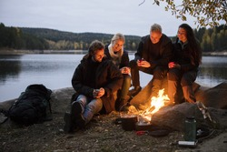 Friends With Coffee Cups Sitting By Campfire On Lakeshore