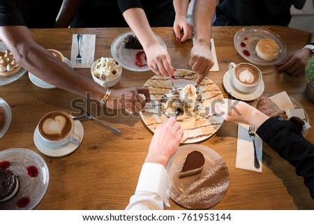 Friends with desserts and coffee, close up.Happy couple sitting around the table and watch football games on TV. Hands holding cups, happy festive moment, luxury celebration concept.  #761953144