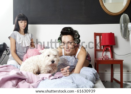 friends with dog watch TV sitting on bed