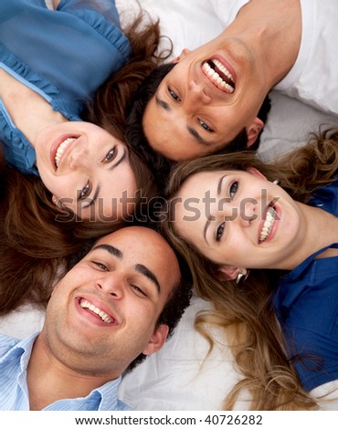 Friends with heads together on the floor smiling