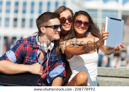 friends with laptop sitting on a steps outdoors