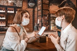 Friends woman met in a cafe and communicate with each other and chat. Wear medical protective masks. An outbreak of the coronavirus epidemic. New rules for social distance and isolation