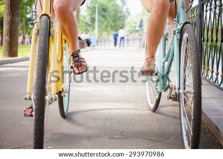 Friends women riding and travel by vintage city bicycles like concept of healthy lifestyle and sport. Bottom view, bicycles moving forward