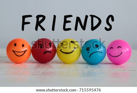 Friends wording on emotions balls background ,Happy Smiley face yellow ball , orange and pink. Sadness ball in blue and madness ball in red. Self made hand draw balls. #715595476