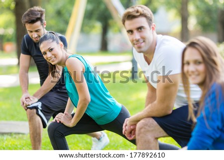 Friends work out in park. Selected focus on face of man in white shirt