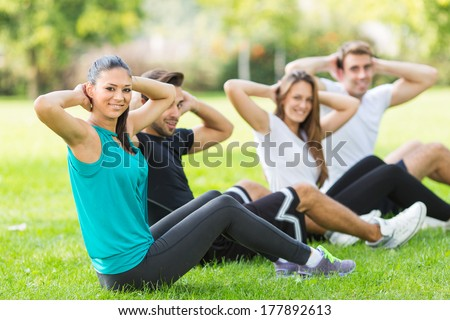 Friends work out in park. Selected focus on face of woman in green shirt