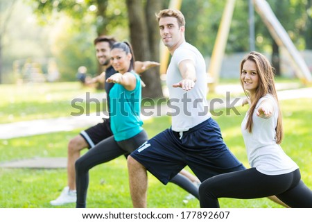 Friends work out in park. Selected focus on face of woman in white shirt