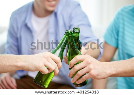 friendship, alcohol, people, celebration and holidays concept - close up of male friends drinking and clinking beer bottles at home #401254318