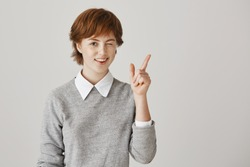 Friendship and emotions concept. Positive and attractive redhead girl with short hair and freckles, winking while smiling and showing victory or peace gesture, greeting friend or posing at camera.