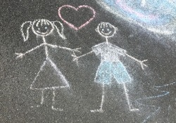 Friendship and love, children's drawing outdoors on the sidewalk. Painting with colored chalks. The child attracted his sense of affection.
