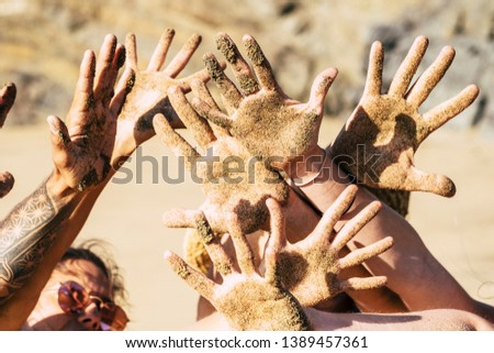Friendship anmd happiness and joyful concept with group of young happy people showing and playing with hands dirty of sand at the beach during summer joy holiday vacation outdoor #1389457361