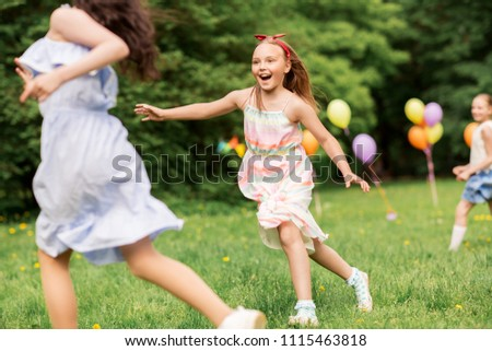 friendship, childhood, leisure and people concept - group of happy girls or friends playing tag game at birthday party in summer park