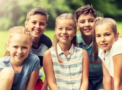 friendship, childhood, leisure and people concept - group of happy kids or friends in summer park