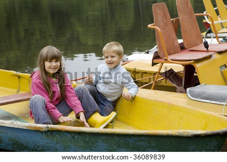 Friendship. Children playing in yellow boat. Summer time