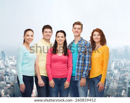 friendship, city life and people concept - group of smiling teenagers over city background