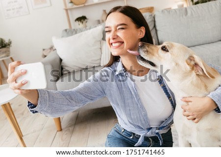 Friendship Concept. Excited beautiful caucasian woman taking selfie with her dog at home, puppy licking her face