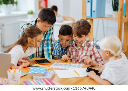 Friendship. Cute sweet company of classmates sitting in a classroom while doing homework