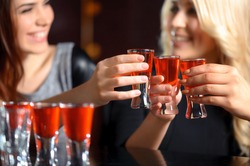 Friendship forever. Selective focus on three shots with red beverage and smiling girls in blurry holding glasses