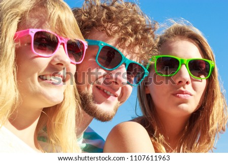 Friendship happiness summer holidays concept. Group of friends boy two girls in colorful sunglasses having fun outdoor, joy playful mood. #1107611963