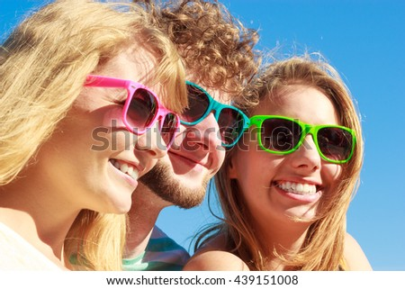 Friendship happiness summer holidays concept. Group of friends boy two girls in colorful sunglasses having fun outdoor, joy playful mood. #439151008