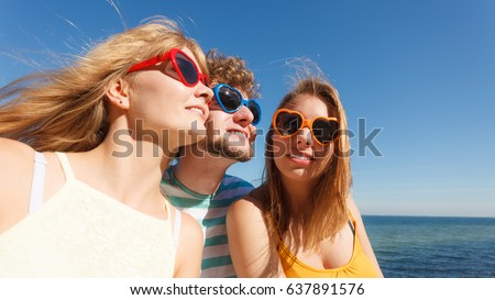 Friendship happiness summer holidays concept. Group of friends boy two girls in sunglasses having fun outdoor,  joy playful mood. #637891576