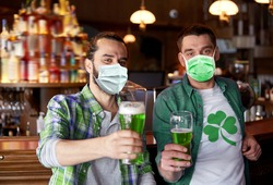friendship, health and st patrick's day concept - happy male friends wearing face protective medical mask for protection from virus disease drinking green beer at bar or pub