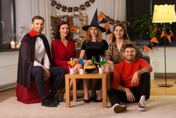 friendship, holiday and people concept - group of happy smiling friends in halloween costumes of vampire, devil, witch and cheetah at home party at night