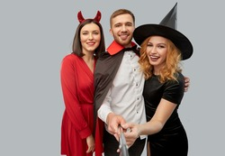 friendship, holiday and people concept - group of happy smiling friends in halloween costumes of witch, devil and vampire taking picture by selfie stick over grey background