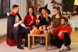friendship, holiday and people concept - group of happy smiling friends in halloween costumes of vampire, devil, witch and cheetah with non-alcoholic drinks at home party at night