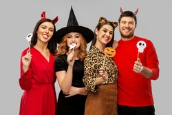 friendship, holiday and photo booth concept - group of happy smiling friends in halloween costumes of devil, witch and cheetah with party props over grey background