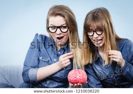 Friendship, human relations concept. Two crazy women friends or sisters wearing jeans shirts and eyeglasses on stick, thinking about solving problem holding fake brain #1210038220