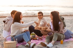 friendship, leisure and fast food concept - group of happy friends eating sandwiches or burgers at picnic on beach in summer
