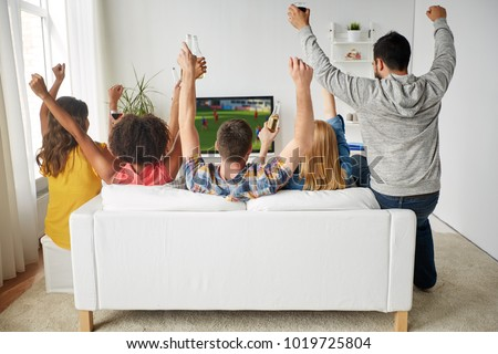friendship, leisure and people concept - happy friends with non-alcoholic beer sitting on sofa and watching soccer or football game on tv at home