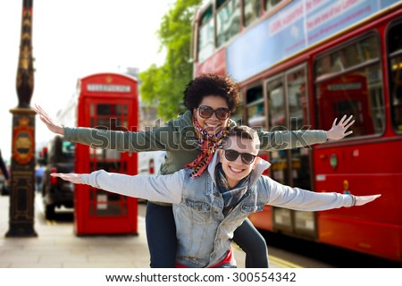 friendship, leisure, international, freedom and people concept - happy teenage couple in shades having fun over london city bus on street background