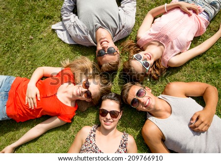 friendship, leisure, summer and people concept - group of smiling friends lying on grass in circle outdoors #209766910