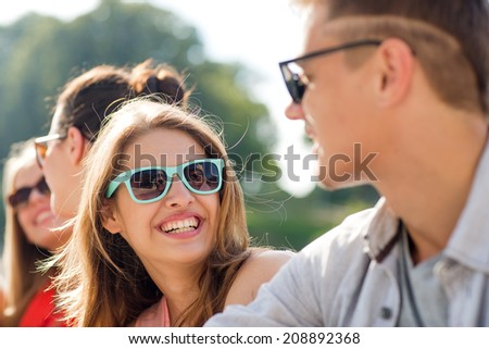 friendship, leisure, summer and people concept - group of smiling friends sitting on city street #208892368