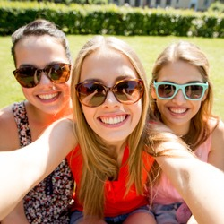 friendship, leisure, summer, technology and people concept - group of smiling teen girls taking selfie with smartphone camera or tablet pc in park