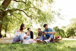 friendship, leisure, technology and people concept - group of friends with smartphones chilling on picnic blanket at summer park