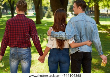 Friendship love jealousy adultery polygamy concept. Love triangle. Young woman in relationship with two men. #744104368