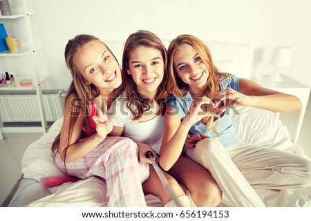 friendship, people, pajama party and technology concept - happy friends or teenage girls with monopod taking selfie at home #656194153
