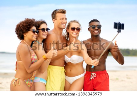 friendship, summer holidays and people concept - group of happy friends taking picture by smartphone on selfie stick on beach and showing thumbs up