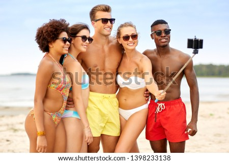friendship, summer holidays and people concept - group of happy friends taking picture by smartphone on selfie stick on beach