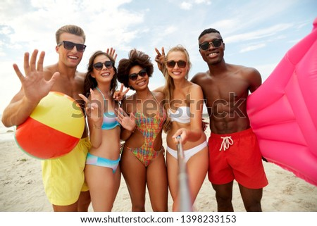 friendship, summer holidays and people concept - group of happy friends taking picture by selfie stick on beach