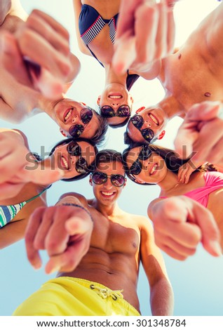 friendship, summer vacation, gesture and people concept - group of smiling friends wearing swimwear and pointing finger on you standing in circle over blue sky