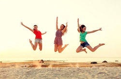 friendship, summer vacation, holidays, party and people concept - group of smiling teen girls jumping on beach