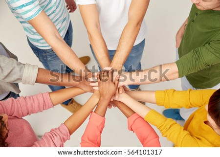 friendship, teamwork and people concept - group of international men and women with hands on top of each other #564101317