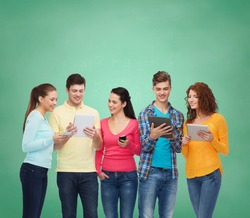 friendship, technology, education, school and people concept - group of smiling teenagers with smartphones and tablet pc computers over green board background